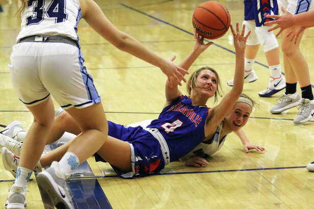 Carlinville's Jill Stayton (4) beats Breese Mater Dei's Shannon Lampe to a loose ball and passes to teammate in the first half Monday night in a semifinal at the Greenville Class 2A Sectional.