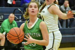 Carrollton's Libby Meuth (left) looks to the basket after getting past Father McGivney's Macy Hoppes on Monday night in a semifinal at the Centralia CORL Class 1A Sectional.