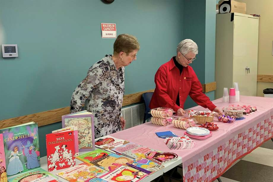 Joan Boroff, left, and Jerena Keys, of the General Federation of Women's Club, set out snacks Wednesday for a Valentine's Day party at the Big Rapids Public Library. (Pioneer photo/Julie Norwood)