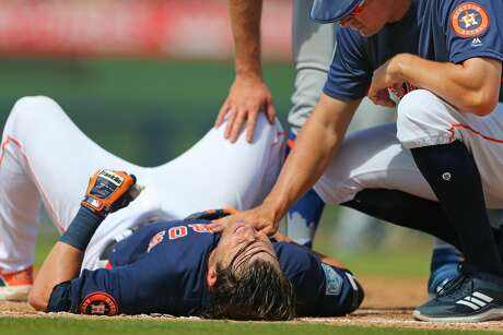 WEST PALM BEACH, FL - MARCH 11: Josh Reddick #22 of the Houston Astros is looked after by first base coach Don Kelly after grounding out and being tagged hard in the face by first baseman Pete Alonso #20 of the New York Mets during the fifth inning of a spring training baseball game at Fitteam Ballpark of the Palm Beaches on March 11, 2019 in West Palm Beach, Florida. The Astros defeated the Mets 6-3. (Photo by Rich Schultz/Getty Images)