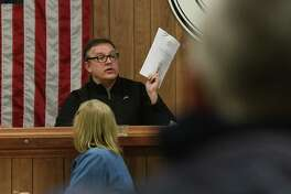 Heinz Noeding holds up the meeting agenda as people attend a town board meeting on Monday, Feb. 17, 2020 in Petersburgh, N.Y. The town board is considering whether to cap the amount of any settlement over PFOA contamination in a landfill Petersburgh shares with neighboring Berlin. (Lori Van Buren/Times Union)
