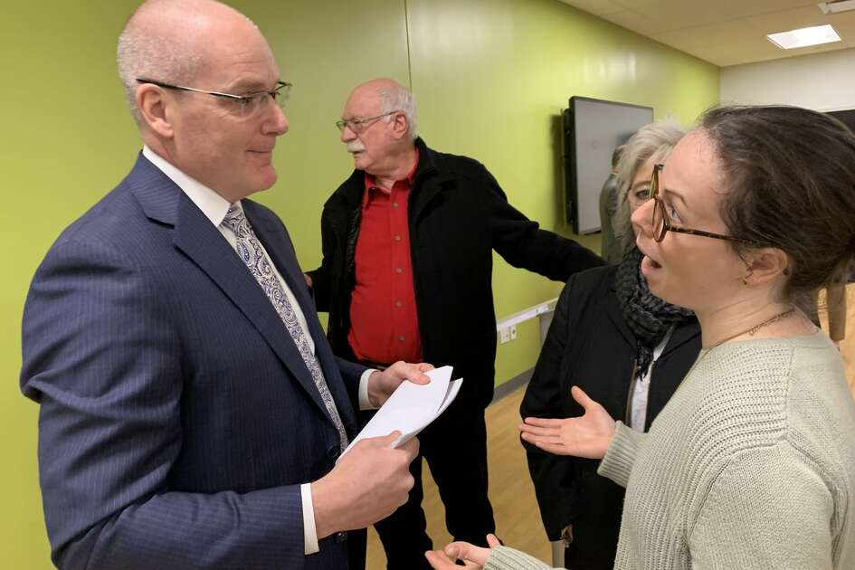 Melanie O'Malley, right, a business owner affected by MyPayrollHR's collapse, speaks with Pioneer Bank CEO Tom Amell during the company's annual shareholder meeting on Tuesday, Feb. 18, 2020.