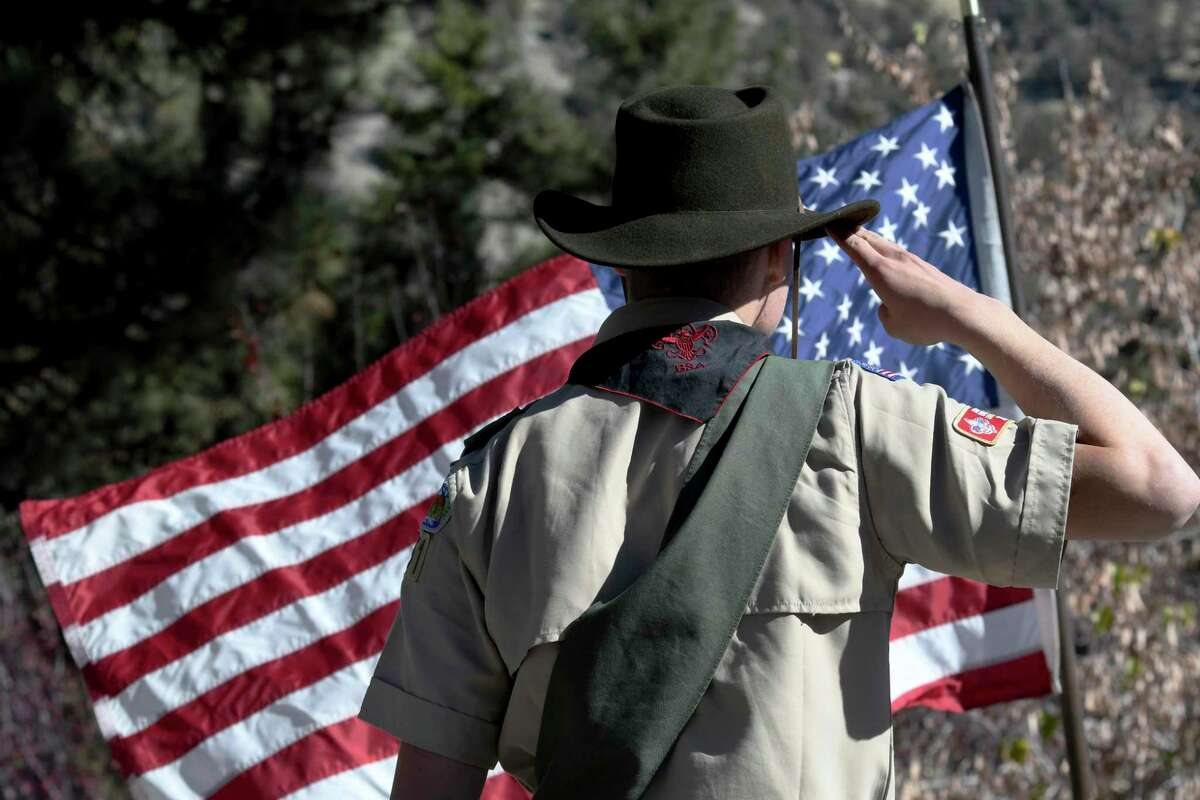FILE - In this Sunday, Nov. 11, 2018 file photo, Boy Scouts lead the Pledge of Allegiance to begin a Veterans Day ceremony in Wrightwood, Calif. Facing a possible bankruptcy due to sex-abuse litigation, the Boy Scouts of America issued a new apology Tuesday, Feb. 11, 2020, to survivors of abuse and announced plans for expanded services to support them. (James Quigg/The Daily Press via AP)