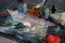 "Flowers adorn actor Kirk Douglas' star on the Hollywood Walk of Fame, Thursday, Feb. 6, 2020, in Los Angeles. Douglas, the muscular actor with the dimpled chin who starred in ""Spartacus,"" ""Lust for Life"" and dozens of other films and helped fatally weaken the Hollywood blacklist, died at 103, on Wednesday. (AP Photo/John Locher)"