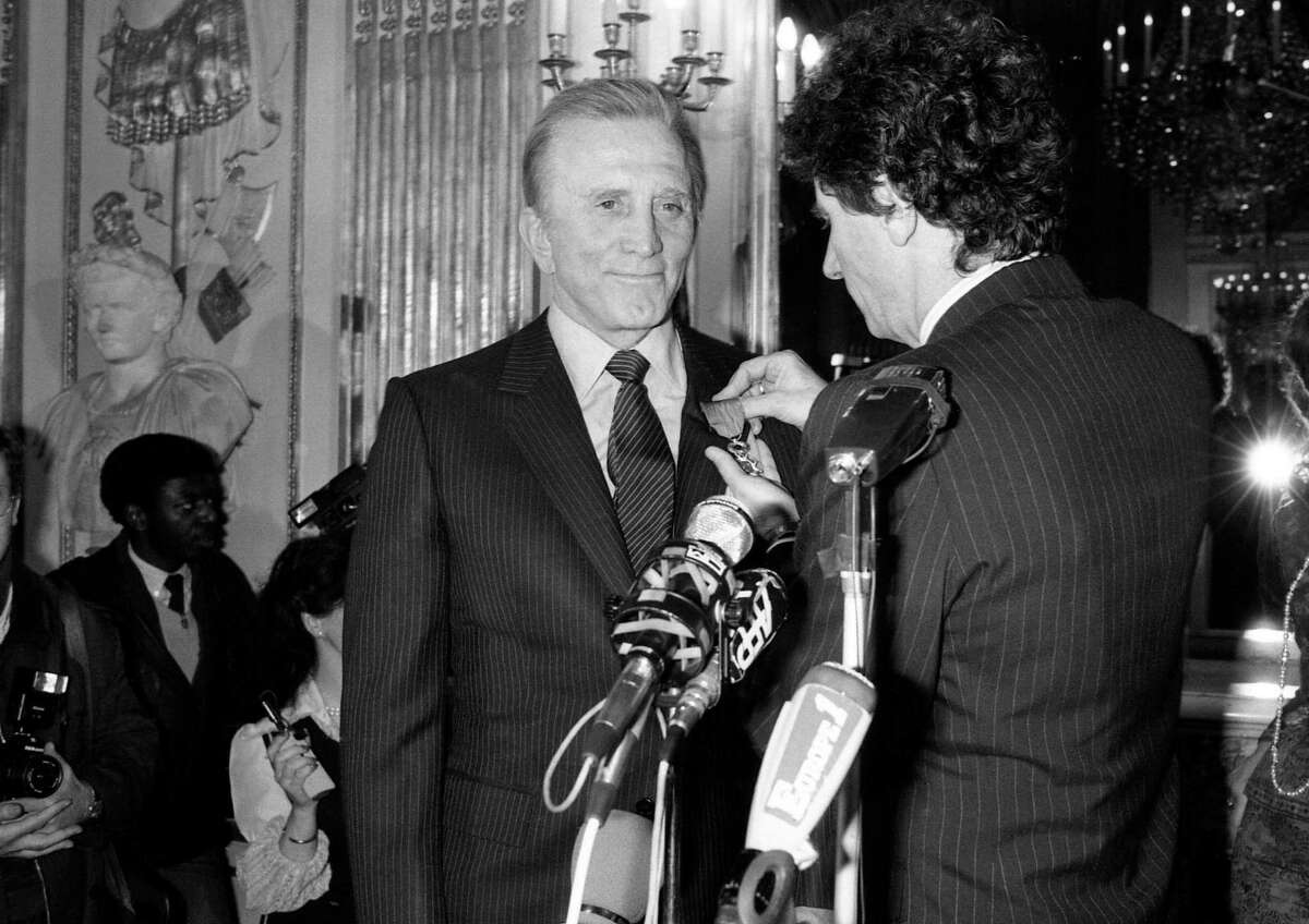 US movie star Kirk Douglas is all smiles as French Culture minister Jack Lang decorated him with the medal of the French Legion of Honor during a ceremony held Friday, March 1, 1985, in Paris. (AP Photo/Lionel Cironneau)