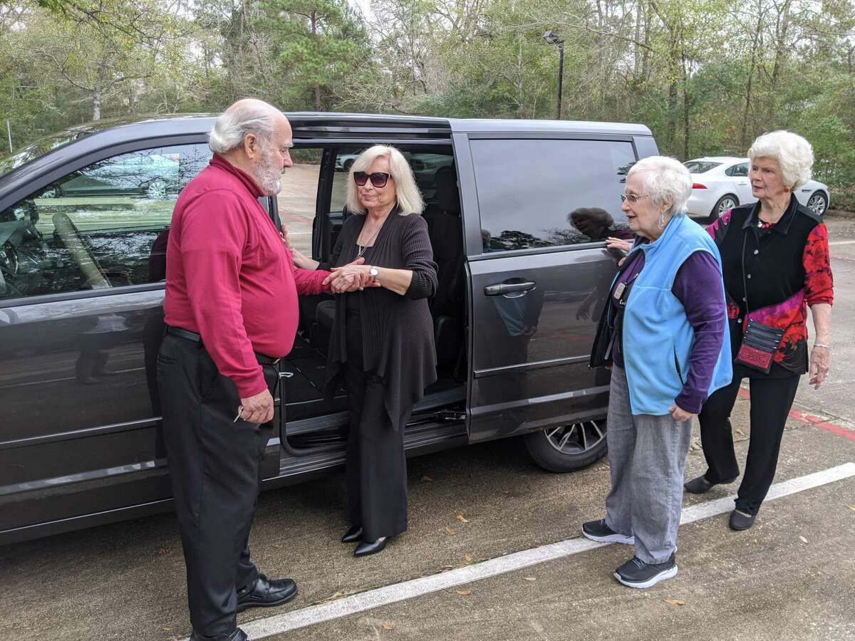 Gerry Saber, left, a volunteer with Aging In Place-The Woodlands, helps Blanca Bradley, a client of the organization, into his van as Beth Kulkarni and Carol Saber wait to load in as well. AIP helps residents of The Woodlands stay social, and gets them where they need to go through volunteer driven rides.