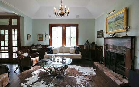 The living room of the Alamo Heights home of Lukin Gilliland. Standout pieces are a cowhide rug and vintage Black Forest seating once used in the Lyndon B. Johnson Suite at the Driskill Hotel in Austin.