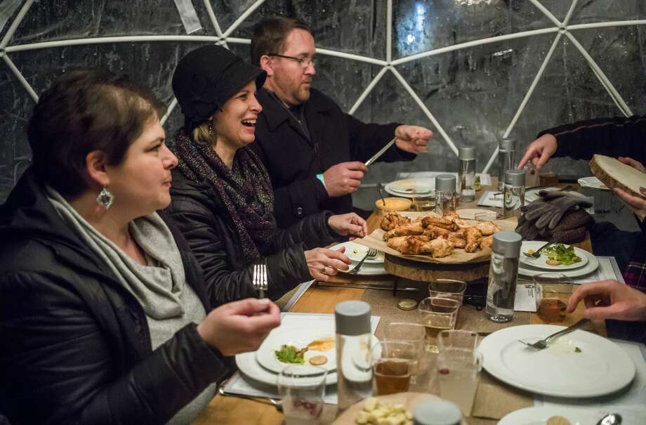 From left, Olivia Vanderleij, Sarah Hocking and David Hocking enjoy an eight-course meal with a group of friends inside a heated igloo tent during the Eat Great Winter event, hosted by Octagon, Monday, Feb. 17, 2020 at Dow Gardens. (Katy Kildee/kkildee@mdn.net) Photo: (Katy Kildee/kkildee@mdn.net)