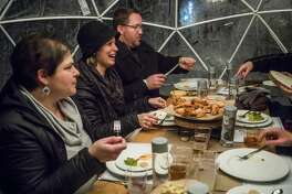From left, Olivia Vanderleij, Sarah Hocking and David Hocking enjoy an eight-course meal with a group of friends inside a heated igloo tent during the Eat Great Winter event, hosted by Octagon, Monday, Feb. 17, 2020 at Dow Gardens. (Katy Kildee/kkildee@mdn.net)