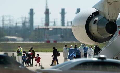 In this Friday, Feb 7, 2020 photo, people arrive from Wuhan, China, aboard a chartered Boeing 747 at Joint Base San Antonio-Lackland in Texas. U.S. officials on Thursday, Feb. 13, announced the country's 15th confirmed case of the new coronavirus — an evacuee from China who had been transported on this flight and was under quarantine in Texas. The patient is now in isolation at a hospital and was reported in stable condition.