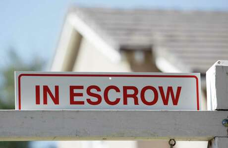 In this photo made Tuesday, Nov. 17, 2009, an 'in escrow' sign has been added to a 'for sale' sign outside a home in Los Angeles. Escrow, the final step to owning your first home, can take well over a month. Here's what you need to know about completing the closing process.