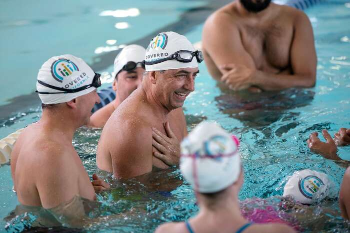 Covered California Executive Director Peter Lee laughs with students during a swim clinic put together by Covered California at the Presidio YMCA in San Francisco, Calif. on Wednesday, January 29, 2020.