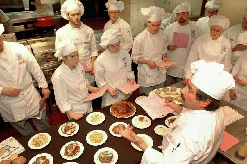 Instructor Chef Rocco Verrigni, right, speaks about different potato recipes that are displayed on the table in front of him to his students during a food lab class at the Schenectady Community College,Thursday, Dec. 1, 2005.