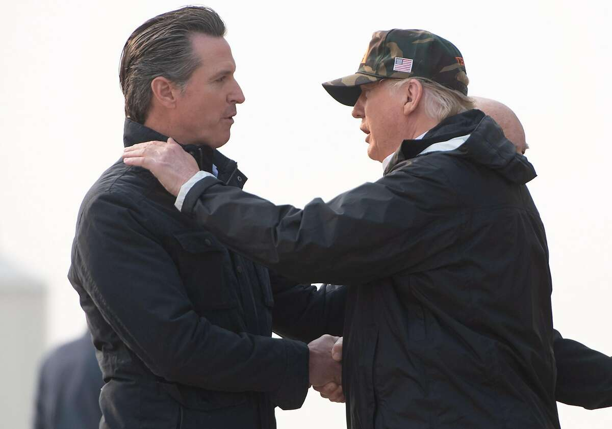 """(FILES) In this file photo taken on November 17, 2018 US President Donald Trump greets California Governor-elect Gavin Newsom (L) as he disembarks from Air Force One upon arrival at Beale Air Force Base in California, as he travels to view wildfire damage. - In a rebuke to President Donald Trump, the governor of California on February 11, 2019 was set to sign an order to pull most of the National Guard troops deployed on the Mexico border. Governor Gavin Newsom's office said he was signing the order ahead of his State of the State speech on Tuesday.""""The border 'emergency' is a manufactured crisis,"""" according to excerpts of the speech sent to AFP by his office. """"And California will not be part of this political theater."""" (Photo by SAUL LOEB / AFP)SAUL LOEB/AFP/Getty Images"""