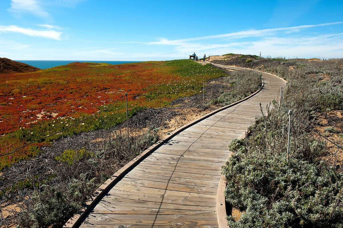 A boardwalk leads across bluff tops to a bayfront lookout at Fort Ord Dunes State Park