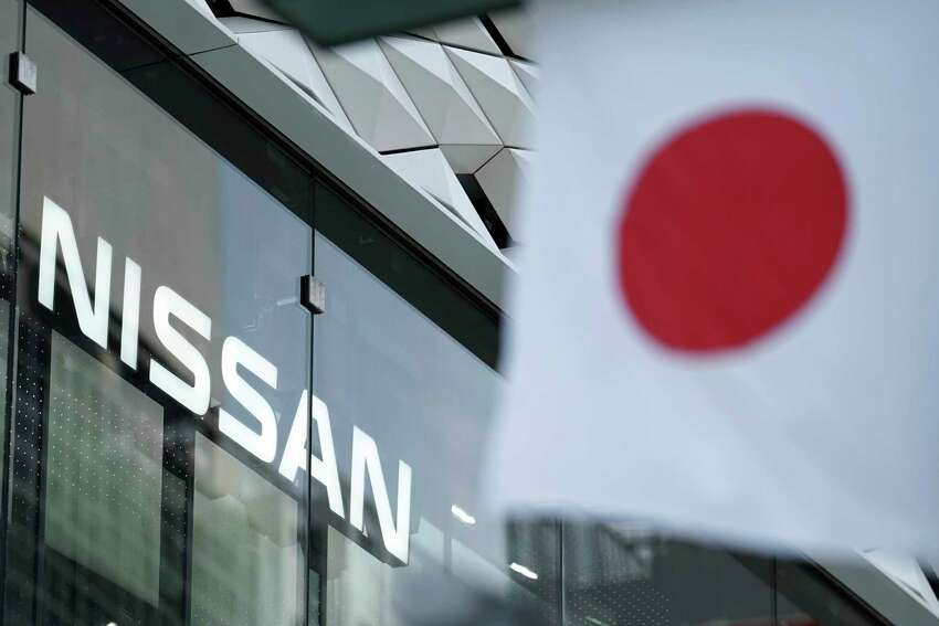 FILE - In this May 10, 2019, file photo, Nissan logo is seen near a Japanese flag at the automaker's showroom in Tokyo. Nissan shareholders unleashed their anger at the Japanese automaker's management Tuesday for crashing stock prices, zero dividends and quarterly losses after the scandal-ridden departure of former Chairman Carlos Ghosn.(AP Photo/Eugene Hoshiko, File)
