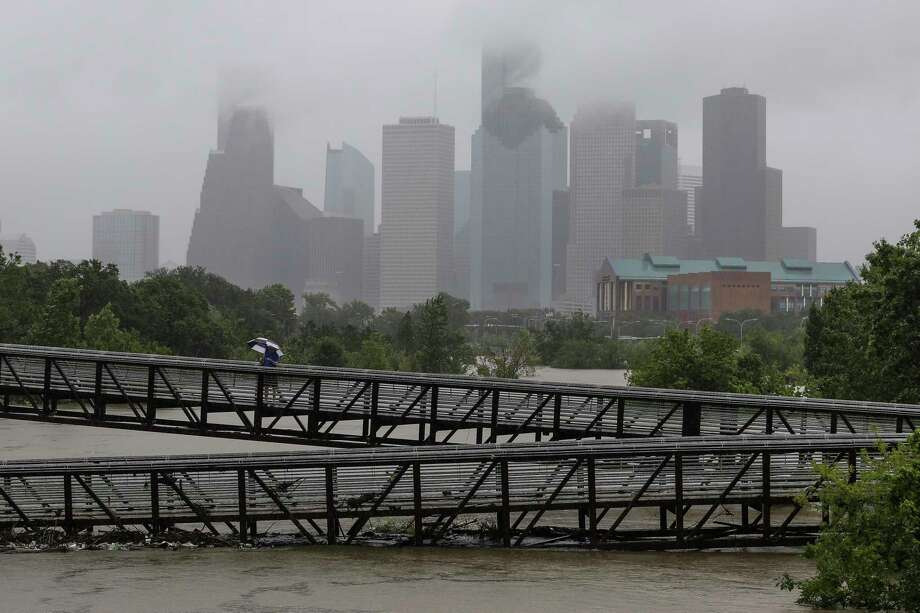 People walk over the Rosemont Pedestrian Bridge to look at a flooded Buffalo Bayou as Hurricane Harvey continues to dump rain over downtown Houston Tuesday, Aug. 29, 2017. Photo: Michael Ciaglo, Staff File Photo/Houston Chronicle / Michael Ciaglo