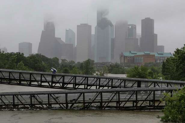 People walk over the Rosemont Pedestrian Bridge to look at a flooded Buffalo Bayou as Hurricane Harvey continues to dump rain over downtown Houston Tuesday, Aug. 29, 2017.