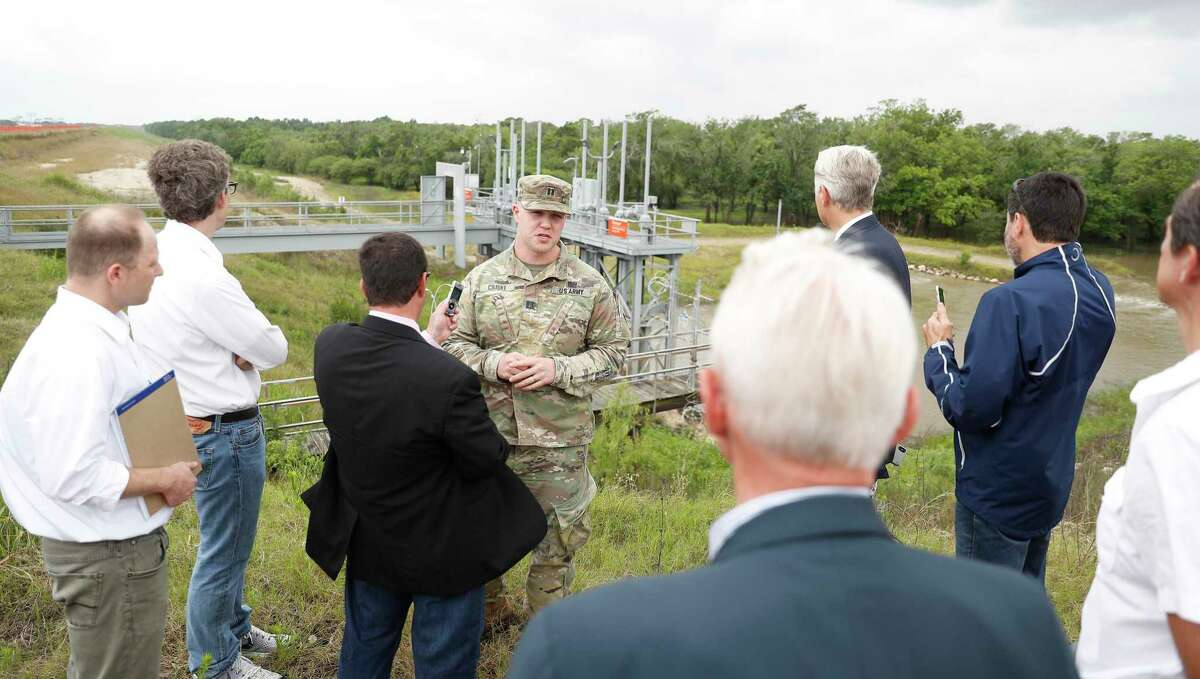 Captain Charles Ciliske with the US Army Corps of Engineers is audio recorded by court reporter David Lee as U.S. Judge Charles Lettow, foreground, listens to his testimony on the top of Barker Reservoir, as the homeowners suing after Harvey went out to view homes in the Addics and Barker Dam areas, in Houston, Wednesday, May 8, 2019.