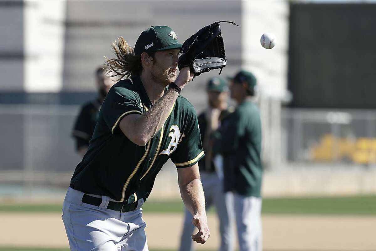 Oakland Athletics' A.J. Puk makes a catch during spring training baseball practice, Thursday, Feb. 13, 2020, in Mesa, Ariz. (AP Photo/Darron Cummings)