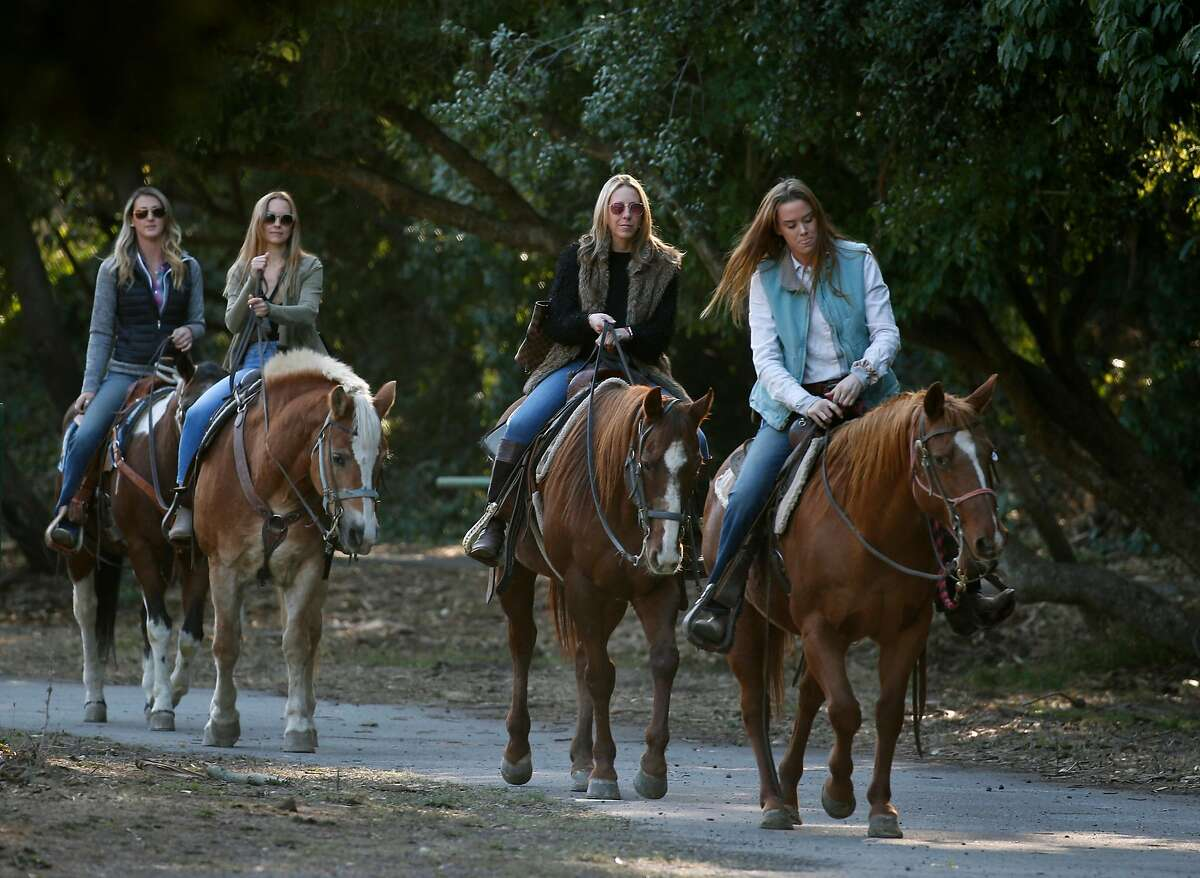 Grace Riddle (right) leads a trail ride on horseback for Koren Cohen (second from right) and Karolina Dadej (second from left) at the Bercut Equitation Field at Golden Gate Park in San Francisco, Calif. on Saturday, Nov. 2, 2019. Bringing up the rear is guide Ashley Molnar. Chaparral Ranch is providing riding lessons and trail rides at the park for the first time in nearly 20 years.