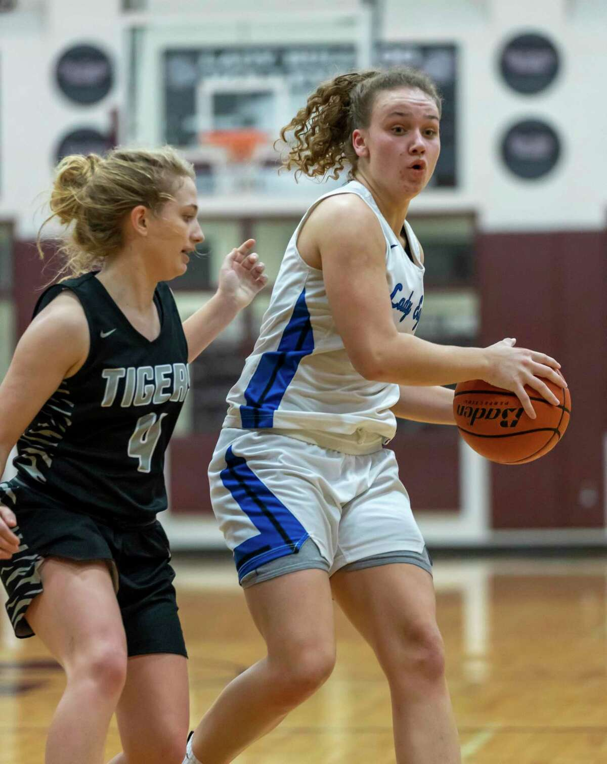 New Caney power forward Abigail Lynch (30) protects the ball from A&M consolidated guard Claire Sisco (4) in a Region III-5A bi-district girls basketball playoff during the second half at Magnolia High School in Magnolia, Tuesday, Feb. 18, 2020.