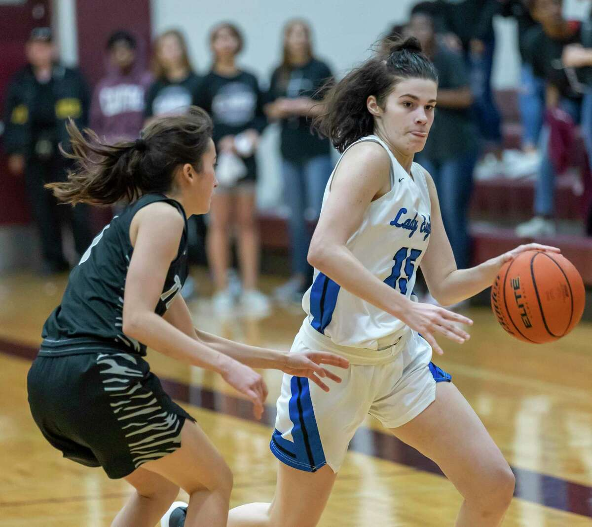 New Caney power forward Michael Mize (15) dribbles the ball toward the basket while under pressure from A&M Consolidated guard Sarah Hathorn (1) in a Region III-5A bi-district girls basketball playoff during the second half at Magnolia High School in Magnolia, Tuesday, Feb. 18, 2020.