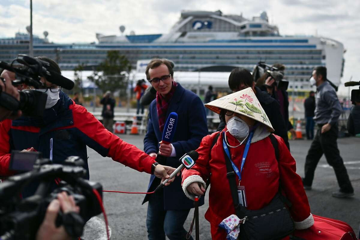 A passenger (right) leaves on foot after disembarking the Diamond Princess cruise ship (back) in quarantine due to fears of the COVID-19 at the Daikoku Pier Cruise Terminal in Yokohama, Japan, on Feb. 19, 2020.
