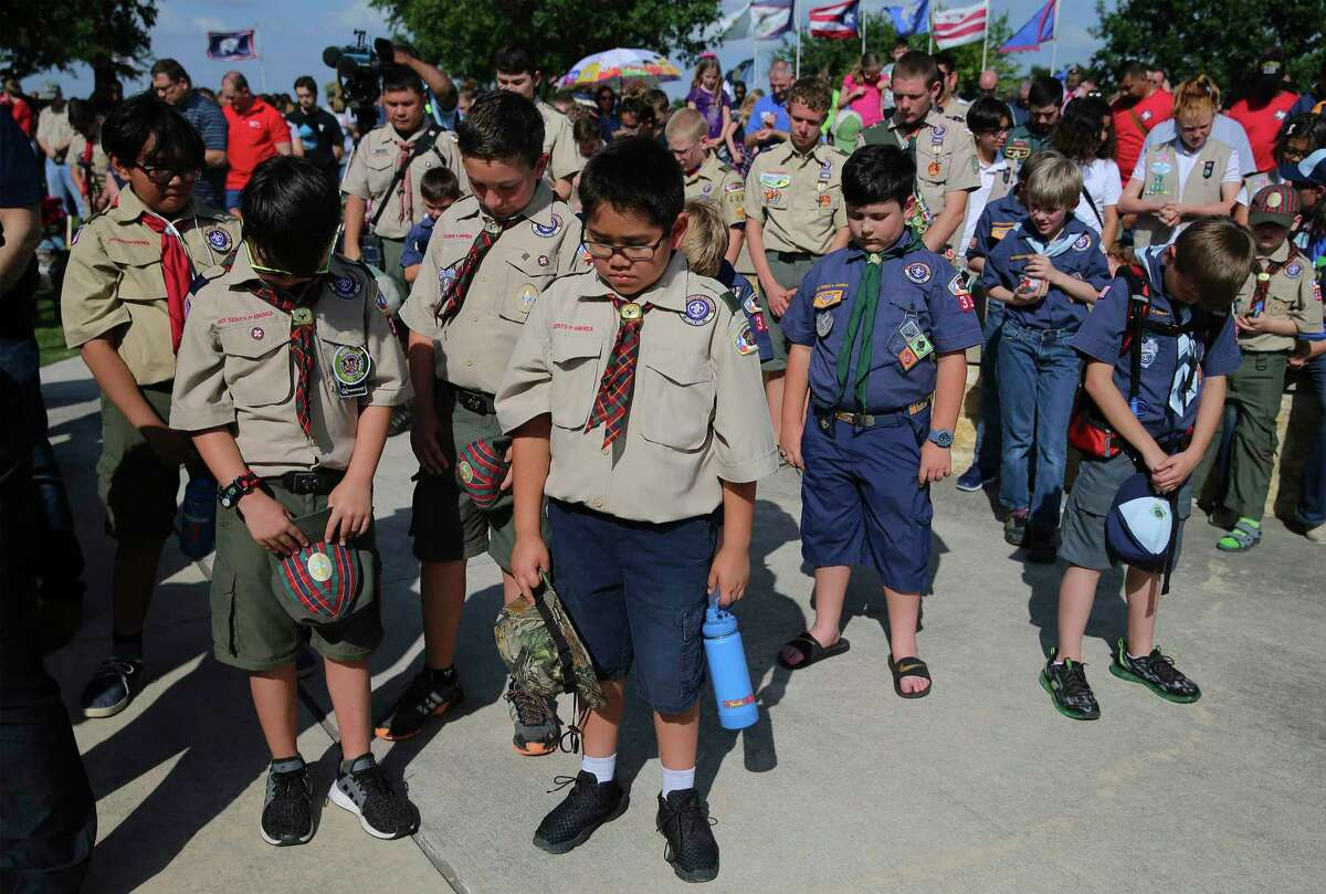 Scouts bow their heads during the invocation as the Boy Scouts of America were among those placing small American flags in front of headstones dotting Fort Sam Houston National Cemetery in May 2019. The national Boy Scouts organization filed for bankruptcy Tuesday but officials with San Antonio's Alamo Area Council of Boy Scouts said it likely won't affect locals because the local council is legally separate from and financially independent of the national group.