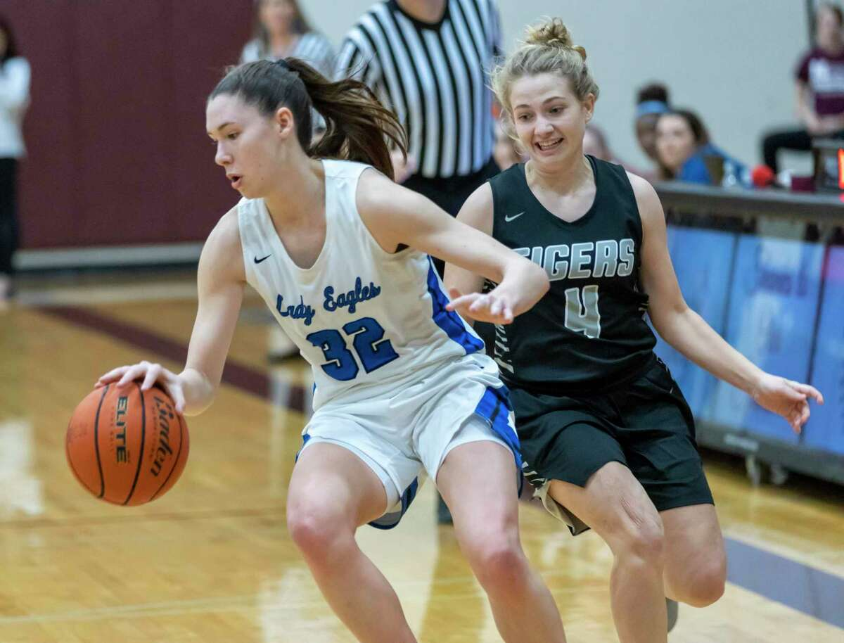 FILE PHOTO - New Caney power forward Tori Garza (32) dribbles the ball passed A&M consolidated guard Claire Sisco (4) in a Region III-5A bi-district girls basketball playoff during the first half at Magnolia High School in Magnolia, Tuesday, Feb. 18, 2020.