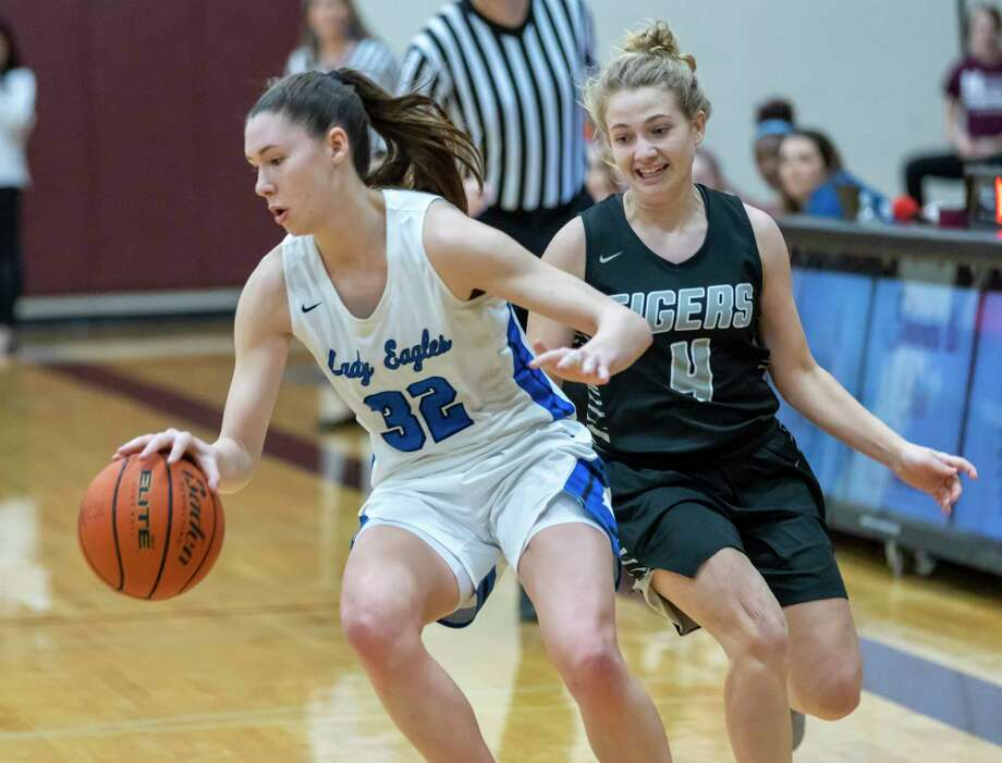 FILE PHOTO — New Caney power forward Tori Garza (32) dribbles the ball passed A&M consolidated guard Claire Sisco (4) in a Region III-5A bi-district girls basketball playoff during the first half at Magnolia High School in Magnolia, Tuesday, Feb. 18, 2020. Photo: Gustavo Huerta, Houston Chronicle / Staff Photographer / Houston Chronicle © 2020