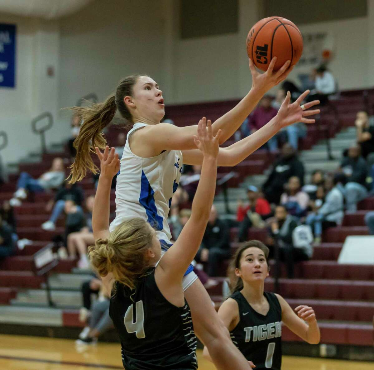 New Caney power forward Tori Garza (32) jumps for the basket while under pressure from A&M consolidated guard Claire Sisco (4) and A&M Consolidated guard Sarah Hathorn (1) in a Region III-5A bi-district girls basketball playoff during the second half at Magnolia High School in Magnolia, Tuesday, Feb. 18, 2020.