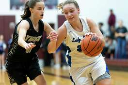 New Caney power forward Abigail Lynch (30) dribbles the ball while under pressure from A&M Consolidated guard Zoe Rich (11) in a Region III-5A bi-district girls basketball playoff during the second half at Magnolia High School in Magnolia, Tuesday, Feb. 18, 2020.