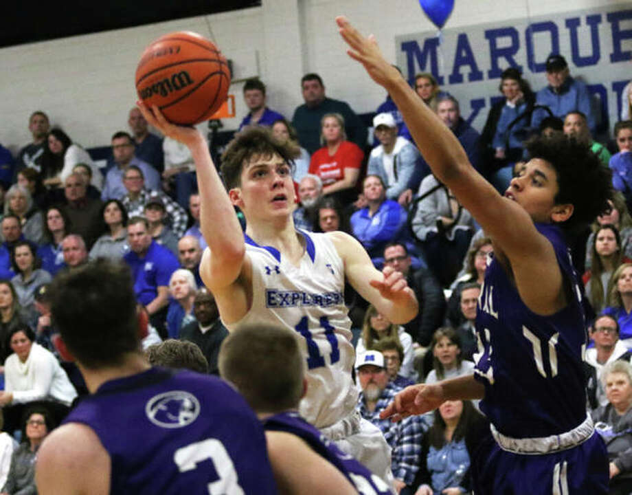 Marquette Catholic's Spencer Cox (11) puts up a shot between Breese Central defenders in the first half of the Explorers' boys basketball victory Tuesday night at Marquette Family Arena in Alton. Photo: Greg Shashack / The Telegraph