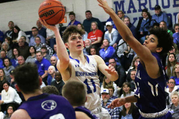 Marquette Catholic's Spencer Cox (11) puts up a shot between Breese Central defenders in the first half of the Explorers' boys basketball victory Tuesday night at Marquette Family Arena in Alton.