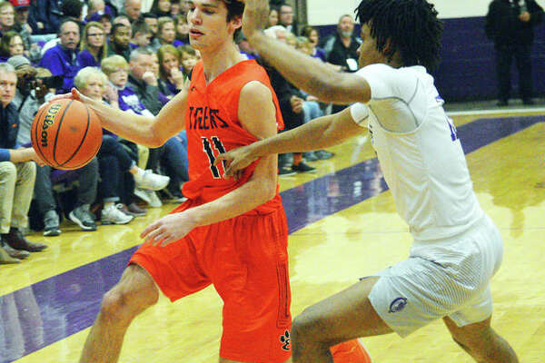 Edwardsville's Brennan Weller, left, drives to the basket during Tuesday's Southwestern Conference game at Collinsville.