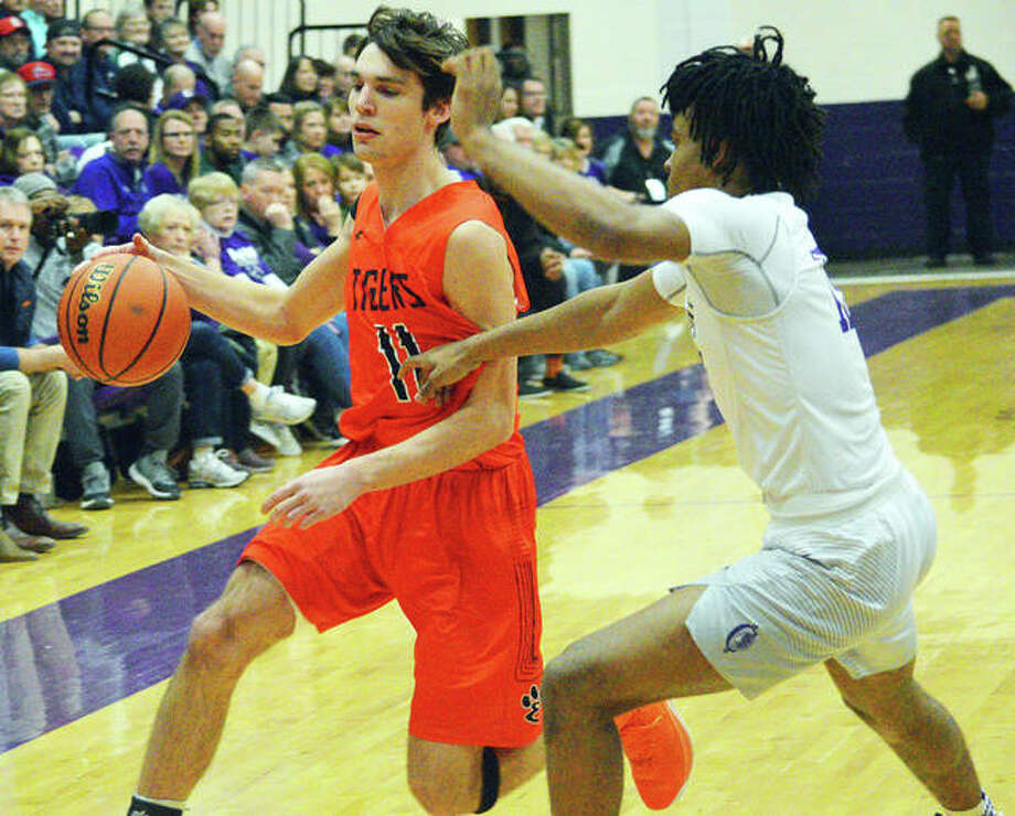 Edwardsville's Brennan Weller, left, drives to the basket during Tuesday's Southwestern Conference game at Collinsville. Photo: Scott Marion / Hearst Midwest