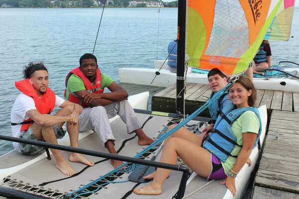 Counselors and campers enjoying the Swim and Sail Program for children with special needs at the Darien YMCA's summer camp.