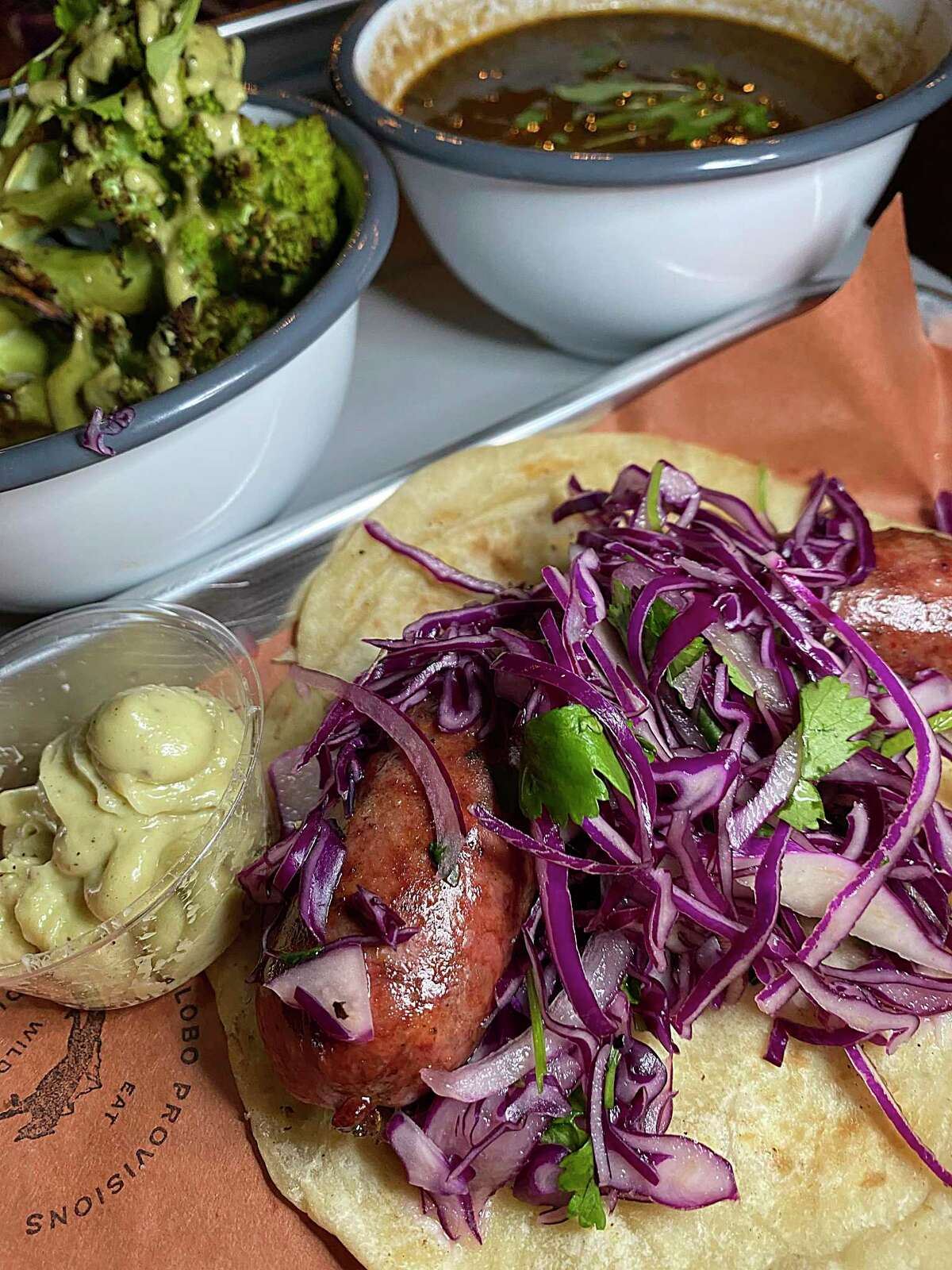 The menu includes a grilled daily vegetable (cauliflower, in this case), heirloom beans and a housemade wild boar hot link sausage with pickled cabbage slaw and garlic aioli at Lobo Provisions.