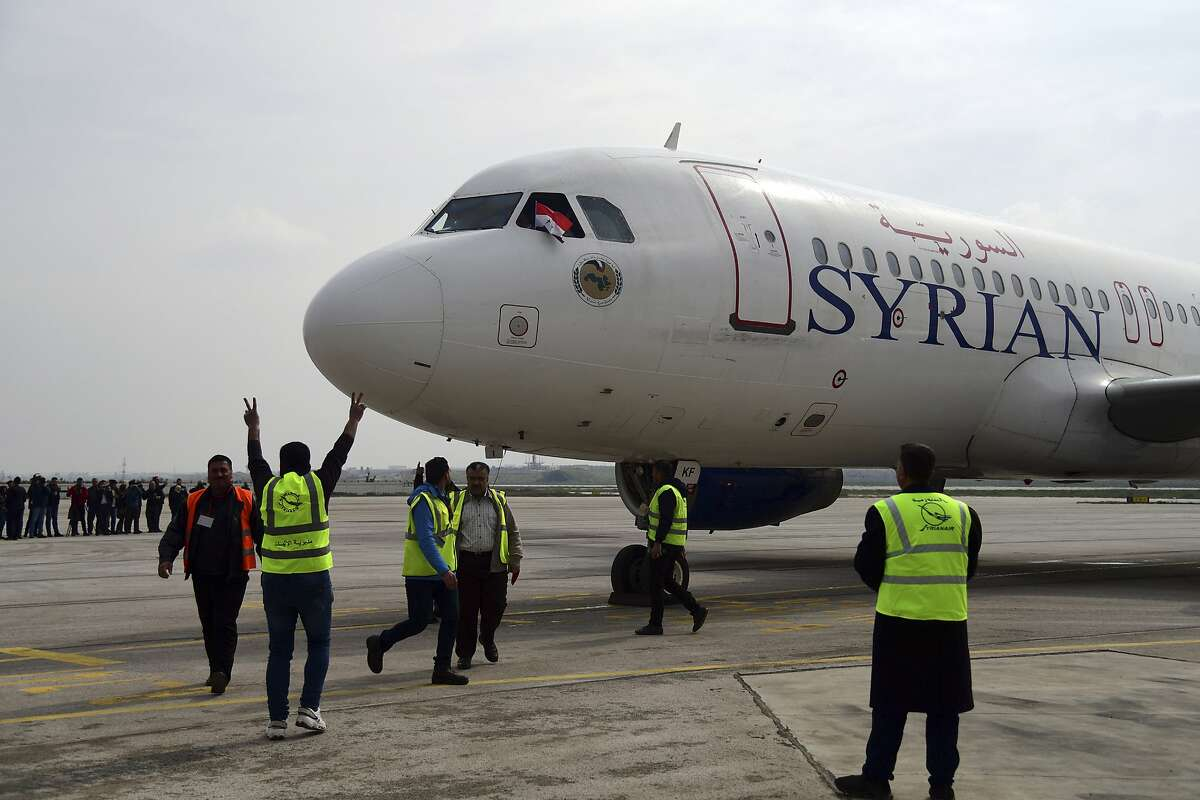 This photo released by the Syrian official news agency SANA, shows workers welcoming a Syrian commercial plane carrying Syrian officials and journalists after it landed at Aleppo Airport, Syria, Wednesday, Feb. 19, 2020. The Syrian commercial flight on Wednesday from Damascus, marked the resumption of internal flights between Syria's two largest cities for the first time since 2012.