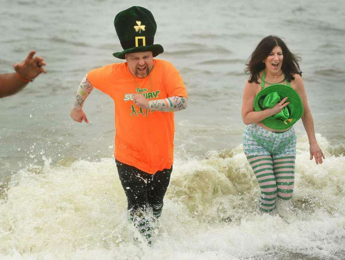 Team Subway members John Sinnott and Paula Kranyak, both of Milford, run from cold waters of the Sound during the Literacy Volunteers of Southern Connecticut's annual Leprechaun Leap at Walnut Beach in Milford, on March 10, 2019.