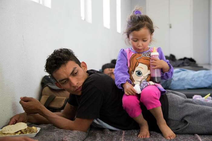 Jennifer, 2, drinks a coke from a bottle while sitting on her father Misael Acosta at the shelter her family are staying at in April 2019 in Ciudad Juárez, Mexico. They were among the first asylum seekers returned to Ciudad Juárez under the Trump administration's policy of making migrants wait in Mexico for their U.S. court dates. On Friday, a California federal court blocked the program, though an appeal to the Supreme Court is likely.