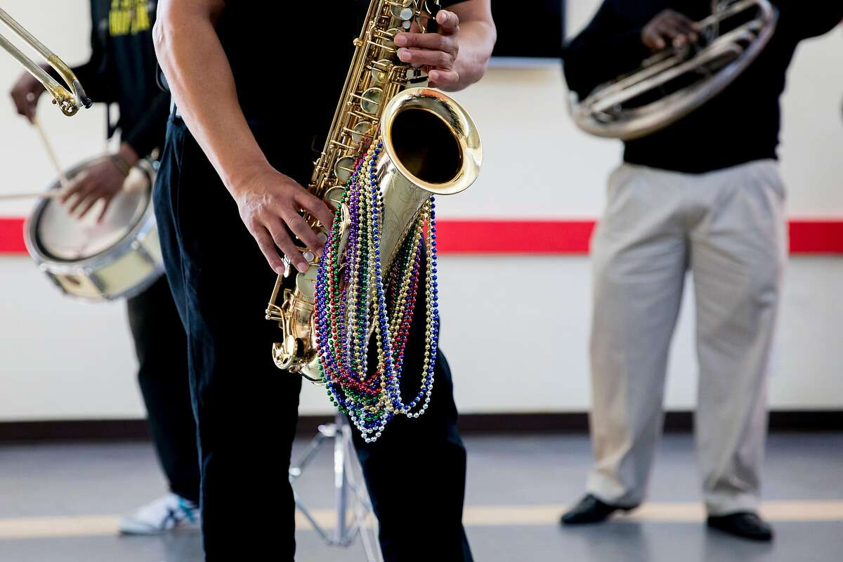 MJ's Brass Bopper Band saxophonist Al Lazard plays with Mardi Gras beads hanging from his instrument while performing during a community Mardi Gras celebration held at the IT Bookman Community Center in the Ingleside neighborhood of San Francisco, Calif. Saturday, February 15, 2020. This local get-together was organized by Ms. Edna James, a longtime New Orleans resident who relocated to the neighborhood following Hurricane Katrina, with support from the Oceanview Library branch manager Lynne Maes.