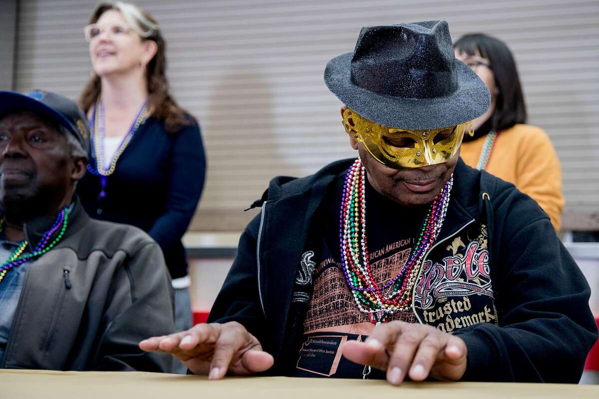 Ingleside resident James Taylor pretends to play piano along with the MJ Brass Bopper Band's music during a community Mardi Gras celebration held at the IT Bookman Community Center in the Ingleside neighborhood of San Francisco, Calif. Saturday, February 15, 2020. This local get-together was organized by Ms. Edna James, a longtime New Orleans resident who relocated to the neighborhood following Hurricane Katrina, with support from the Oceanview Library branch manager Lynne Maes.