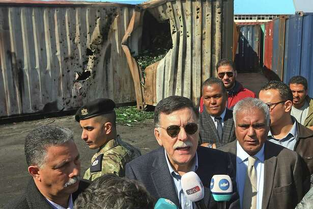 Prime Minister of Libya's UN-recognised Government of National Accord (GNA) Fayez al-Sarraj speaks to the press during his visit to the port in the capital Tripoli after it was hit by rocket fire on February 19, 2020. - Libya's unity government has announced it is halting its participation in UN talks aimed at brokering a lasting ceasefire in the war-torn country where a fragile truce has been repeatedly violated. The pull-out came after a barrage of rocket fire hit a port in the capital Tripoli -- the target of a months-long operation by eastern military commander Khalifa Haftar to oust the Government of National Accord (GNA). (Photo by Mahmud TURKIA / AFP)