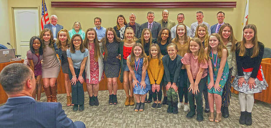 Cheerleaders from both Liberty Middle School and Lincoln Middle School stand with the Edwardsville City Council pose with their medals and trophy after being recognized by the council Tuesday night. Photo: Charles Bolinger | The Intelligencer