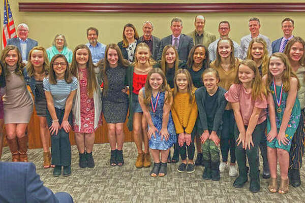 Cheerleaders from both Liberty Middle School and Lincoln Middle School stand with the Edwardsville City Council pose with their medals and trophy after being recognized by the council Tuesday night.