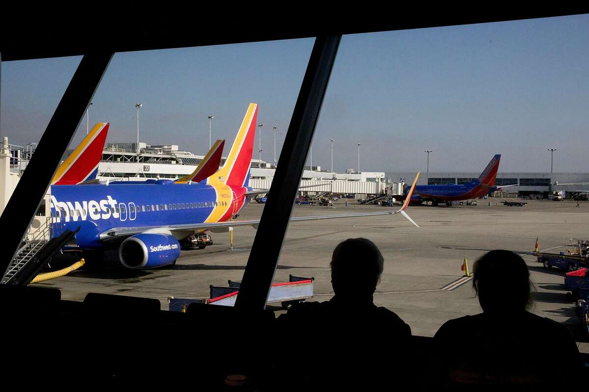 Travelers wait for a Southwest flight at Oakland International Airport on Jan. 30, 2020. A man who refused to pull a face mask over his nose on a flight from a Southwest flight from Oakland to Houston in February 2021 faces a $9,000 fine from the Federal Aviation Administration.