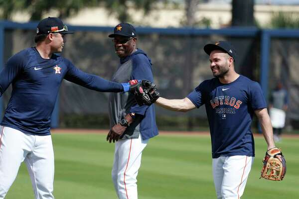 Houston Astros Jose Altuve and Aledmys Diaz high-five after infield drills with manager Dusty Baker Jr. during the Houston Astros spring training workouts at the Fitteam Ballpark of The Palm Beaches, in West Palm Beach , Wednesday, Feb. 19, 2020.
