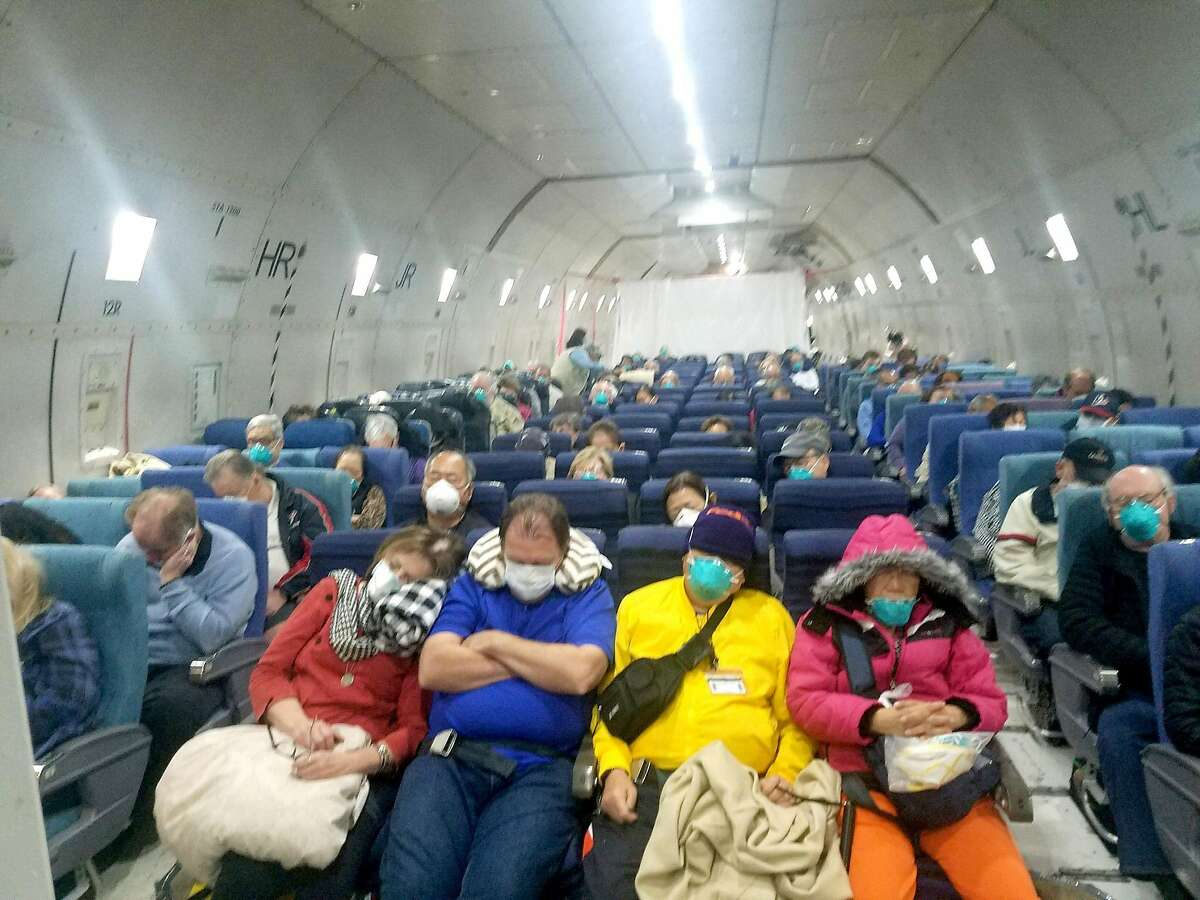 Passengers are seen on a U.S.-chartered cargo jet from Japan to Lackland Air Force Base near San Antonio on Monday. Otis and Carol Menasco were among those aboard the Diamond Princess cruise ship, which saw an outbreak of the COVID-19 coronavirus.